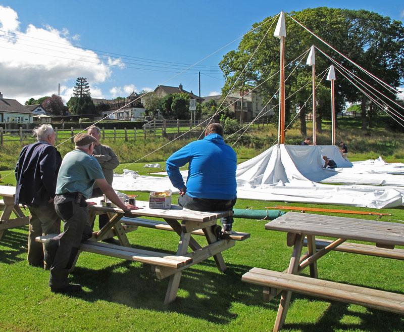 Members watch as the tent is prepared