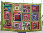 A photo of the anniversary quilt hanging in the show tent.