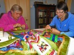 A photo of Elaine and Linda working on the quilt