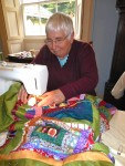 A photo of Marina Lambert sewing up the quilt